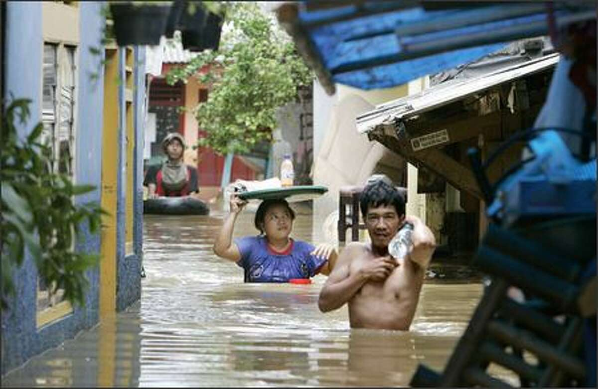 Indonesians carry supplies through the flooded streets of Jakarta Monday. Horse-drawn carts rescued residents from flood-stricken districts in the capital Monday after rain caused rivers flood, killing at least 29 and forcing about 340,000 to flee their homes.