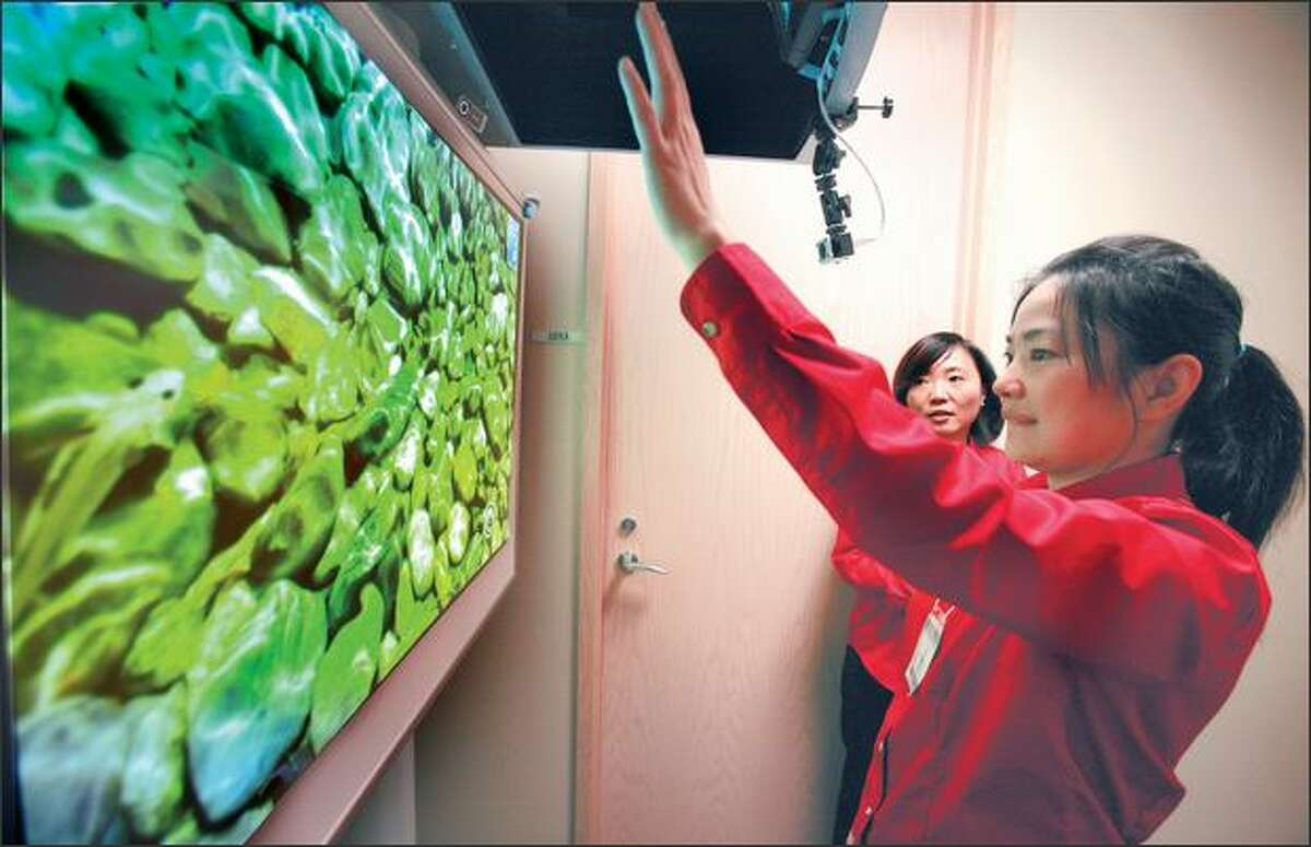 Heng Zhang, project manager in Microsoft's adCenter Labs, demonstrates Air Wave, an interactive display, Tuesday, as Li Li, the lab's group manager, watches.