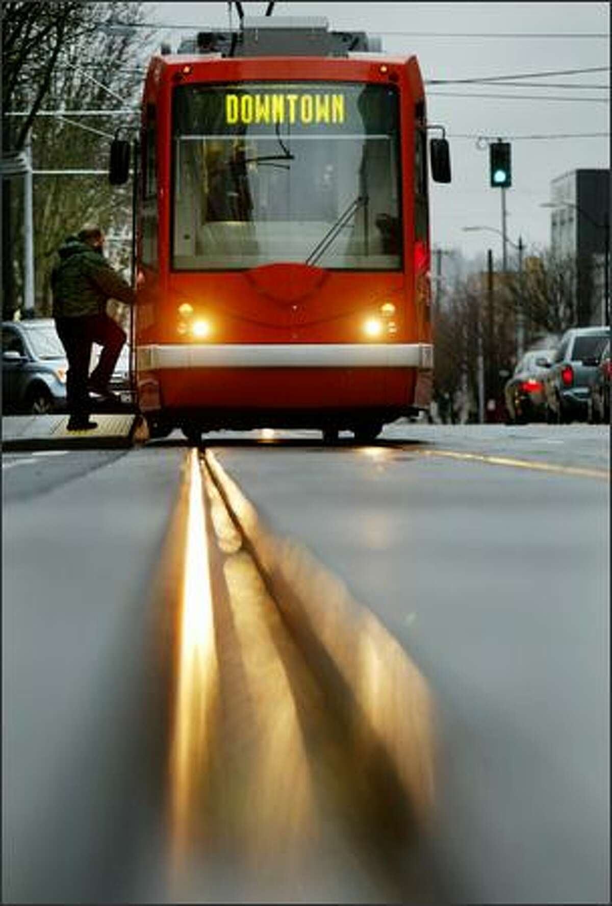 A South Lake Union streetcar picks up a passenger on Westlake Avenue North in Seattle. The city is considering adding lines.