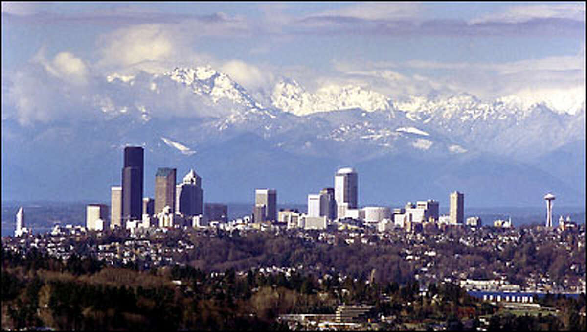 A break in the clouds, some new snow in the Olympic Mountains, and a beam of sunlight on Seattle make for a nice picture. Mercer Island is in the foreground.