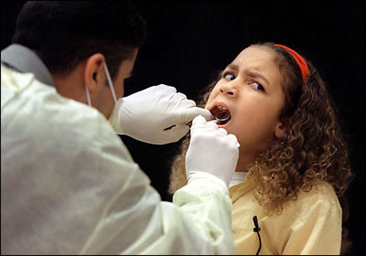 """Whittier Elementary School second-grader Sherry Vernon grimaces as she receives a free dental screening yesterday at the school as part of the """"Watch Your Mouth"""" campaign sponsored by child health advocates. The clinician is also in school -- he's a fourth-year dental student at the University of Washington."""