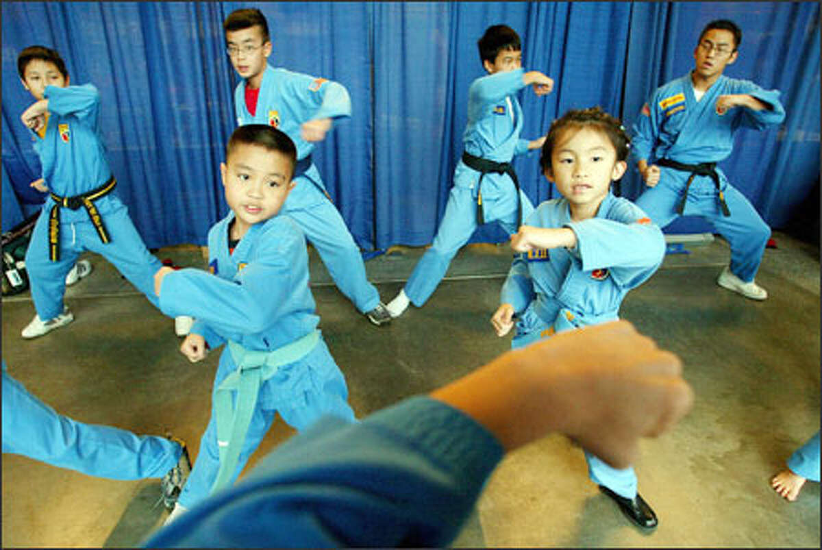 Felix, front left, and Danielle Tran, right, rehearse with other students yesterday before a demonstration of Vo, a Vietnamese martial art, at the Seattle Center's Fisher Pavilion. Members of the Vietnamese community gathered for Tet, the celebration of the new year; 2005 is the year of the rooster.