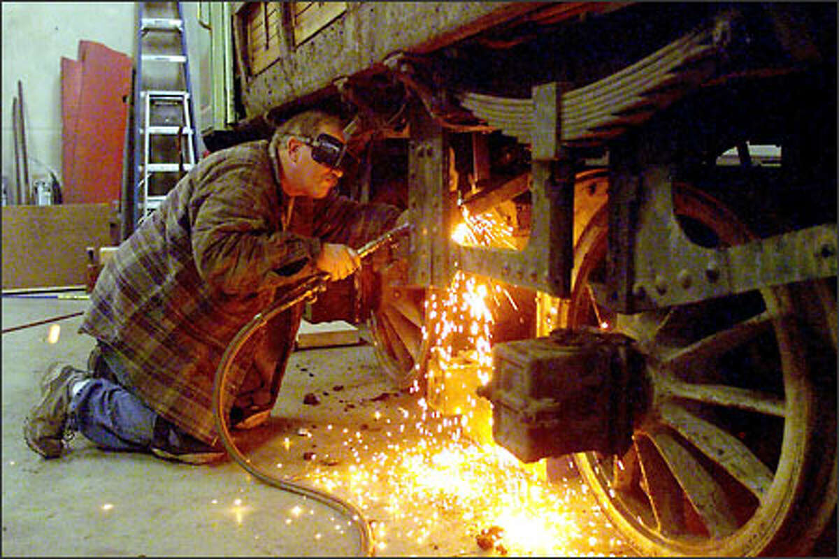 Streetcar buff Tom Mendenhall cuts part of a trolley frame with a welding torch. The cabin will be lifted off so that repairs to the vintage 1895 German-made trolley can begin.