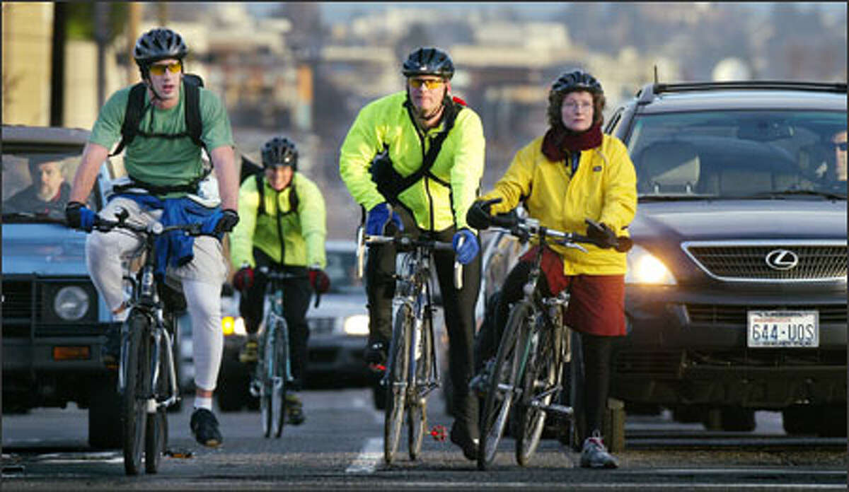 Bike commuters share the road with cars during morning rush hour at the light on Dexter Avenue at Denny Way.