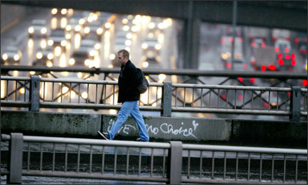 A commuter makes his way back to Capitol Hill from downtown Seattle on Denny Way at the end of the workday as rush-hour traffic snarls Interstate 5 below him.
