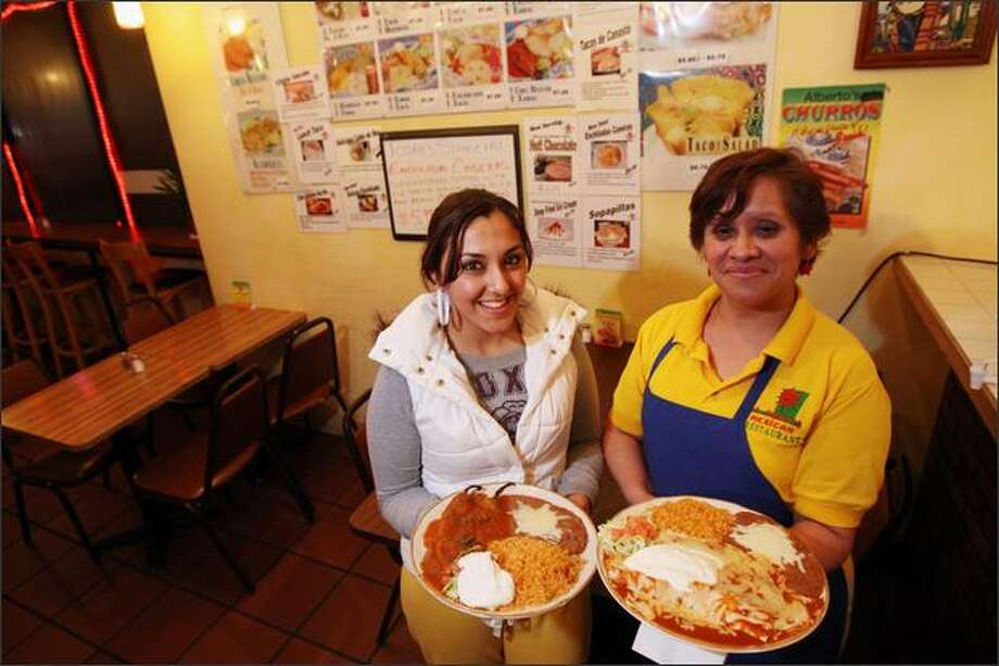 Yolanda Soto, left, and Maria Jimenez, one of the chefs at Mi Charrito Taqueria, hold two of their favorite dishes: chiles tellenos, left, and chipolte enchilades. Photo: Karen Ducey, Seattle Post-Intelligencer / Seattle Post-Intelligencer