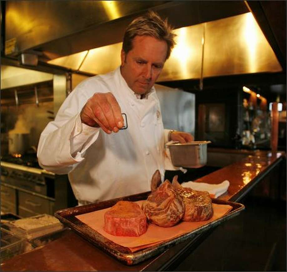 "Executive chef Bradley Dickinson prepares a pair of ""tomahawk chops"" and a Delmonico steak at Daniel's Broiler in Leschi. Photo: Mike Urban, Seattle Post-Intelligencer / Seattle Post-Intelligencer"