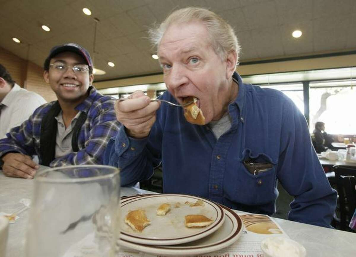 Vince Briant, right, of Sun Lakes, Ariz., takes a bite out of his pancakes while Jon Steffen, of Mesa, Ariz., looks on as hundreds of patrons take advantage of the Denny's free Grand Slam breakfast national giveaway at a local Denny's restaurant in Tempe, Ariz., on Tuesday. (AP Photo/Ross D. Franklin)
