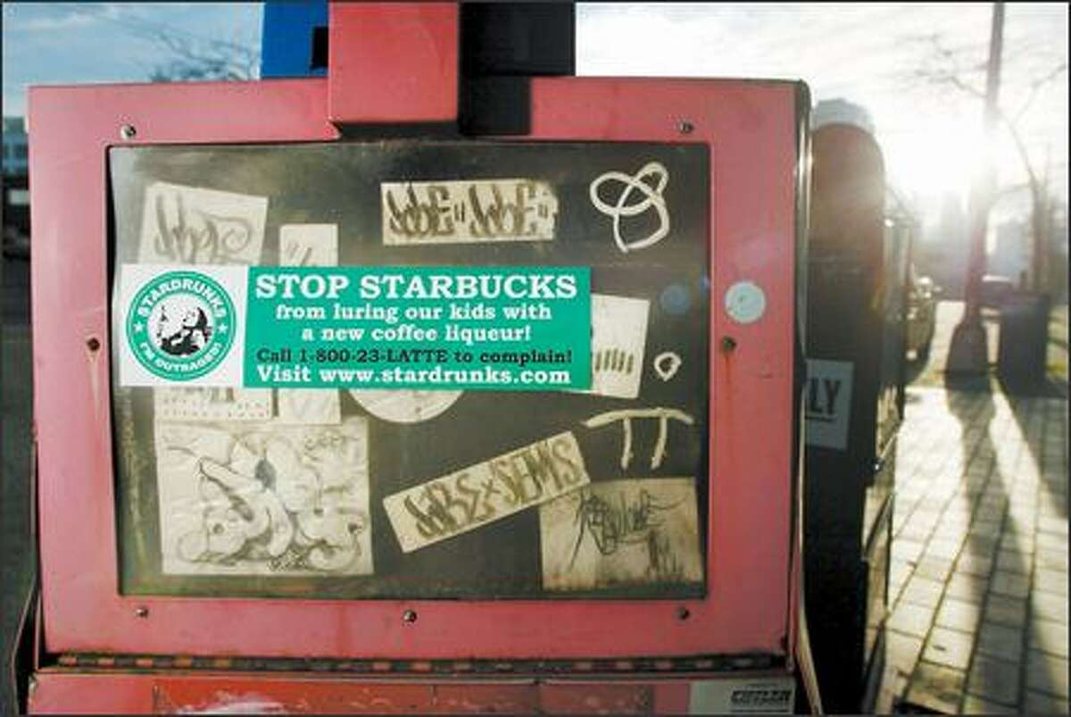 A bumper sticker on a newspaper box accuses Starbucks of luring kids with a new coffee liqueur.