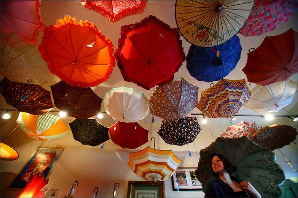 Cheryl Wilson checks out the umbrellas Saturday at Bella Umbrella on Northwest 70th Street. The small shop rents and sells vintage and antique umbrellas. It opened in December