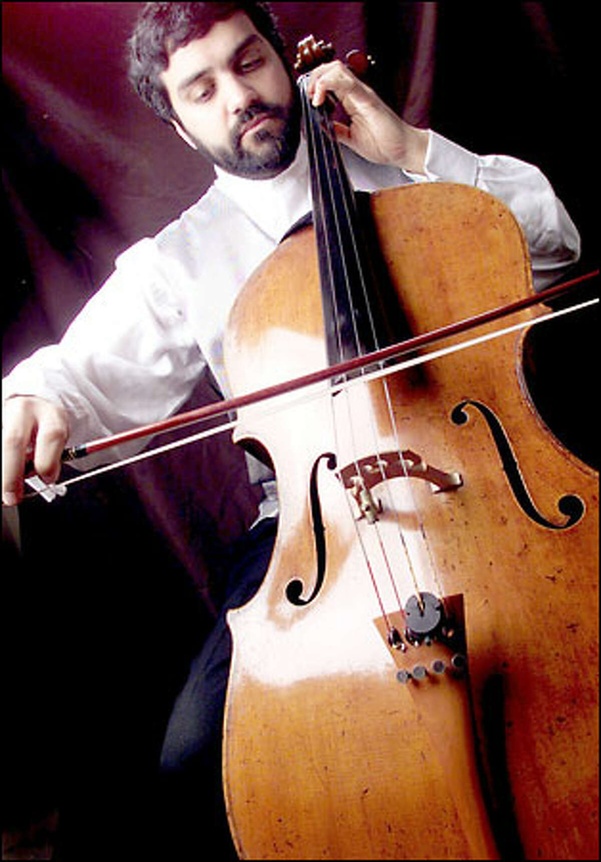 Seattle musician Rajan Krishnaswami draws his bow across his prized cello, a Guadagnini built in Turin, Italy, in 1780. Krishnaswami says the instrument was recently appraised at $1.1 million.