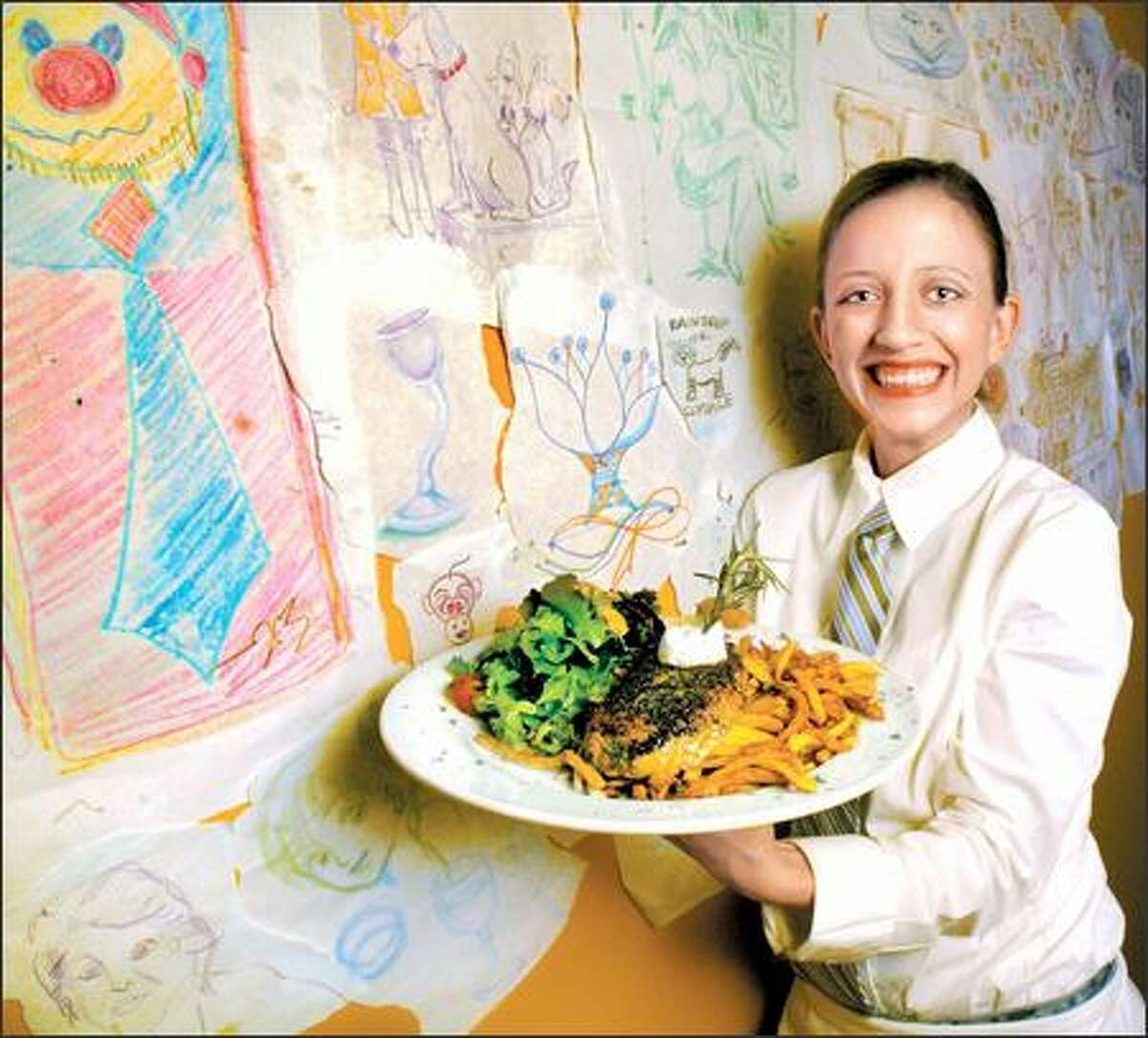Standing next to a wall of customers' crayon art, Rachel Dreyer, a server at XO Bistro, holds a plate of steak frites with steak, salad and fries.