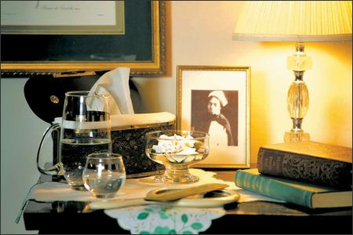A bedside table from Goodwill with a vintage picture frame and books is illuminated by a faux cut-crystal lamp. A Lucite-style woman's purse creatively hides the tissue box.