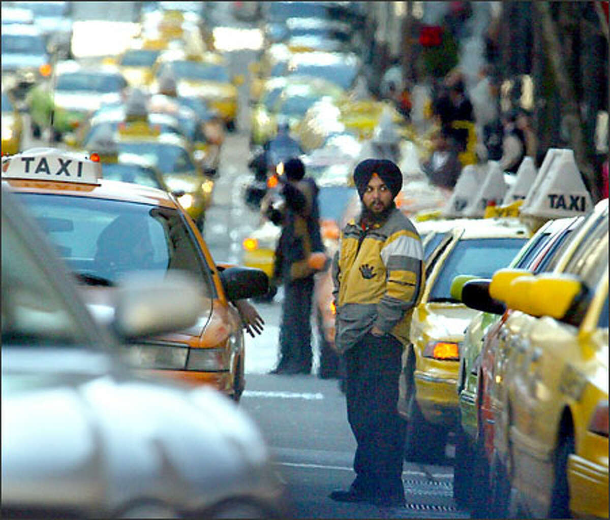 A cabbie stands on Fourth Avenue as other drivers move through the downtown area honking their horns to bring attention to their safety needs.