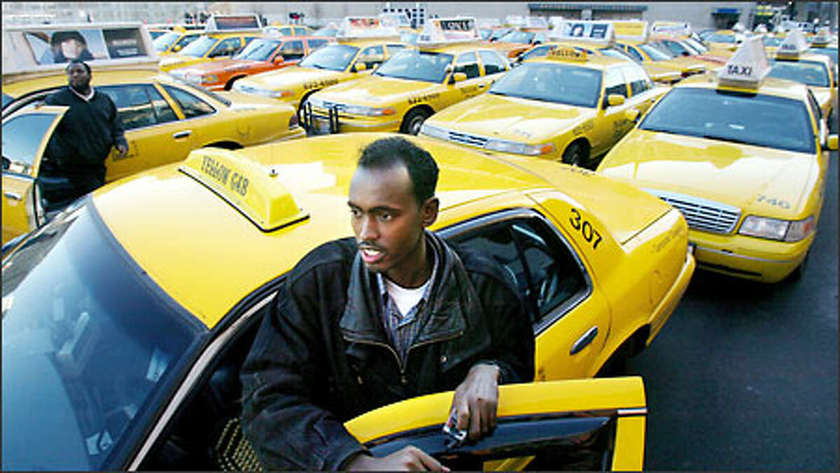 Said Fatah, a Yellow Cab driver for four years, stands by his taxi as drivers congregate on Occidental Avenue South near Seahawks Stadium before moving downtown yesterday.
