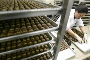 Tang Hue arranges chocolate-covered caramels in paper cups at Fran's Chocolates on Capitol Hill. Valentine's Day is one of the company's busiest times of year.