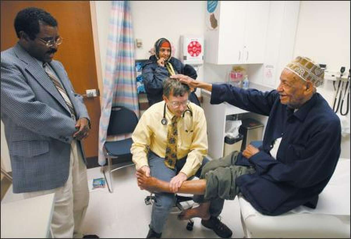 Dr. Frank Stackhouse gets a pat on the head from Aboo Maye Ali, 81, during an exam at Harborview Medical Center's International Clinic. At left is interpreter Gammada Abraham, who translates Somali to English to help Ali and Stackhouse communicate. Ali's daughter, Faduma Aboo Maye, watches in the background.