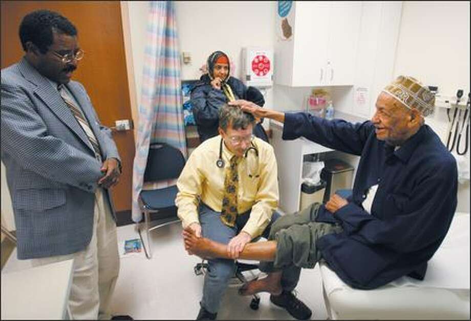Dr. Frank Stackhouse gets a pat on the head from Aboo Maye Ali, 81, during an exam at Harborview Medical Center's International Clinic. At left is interpreter Gammada Abraham, who translates Somali to English to help Ali and Stackhouse communicate. Ali's daughter, Faduma Aboo Maye, watches in the background. Photo: Scott Eklund, Seattle Post-Intelligencer / Seattle Post-Intelligencer