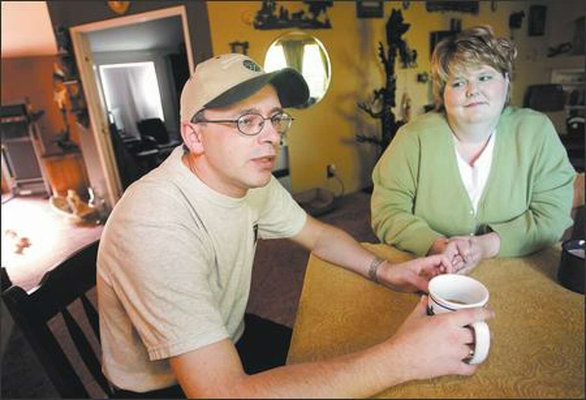 Amnesia victim Jeff Ingram, left, talks during an interview as his then girlfriend Penny Hansen sits beside him at her home Thursday in Olympia. The couple were married on Dec. 31.