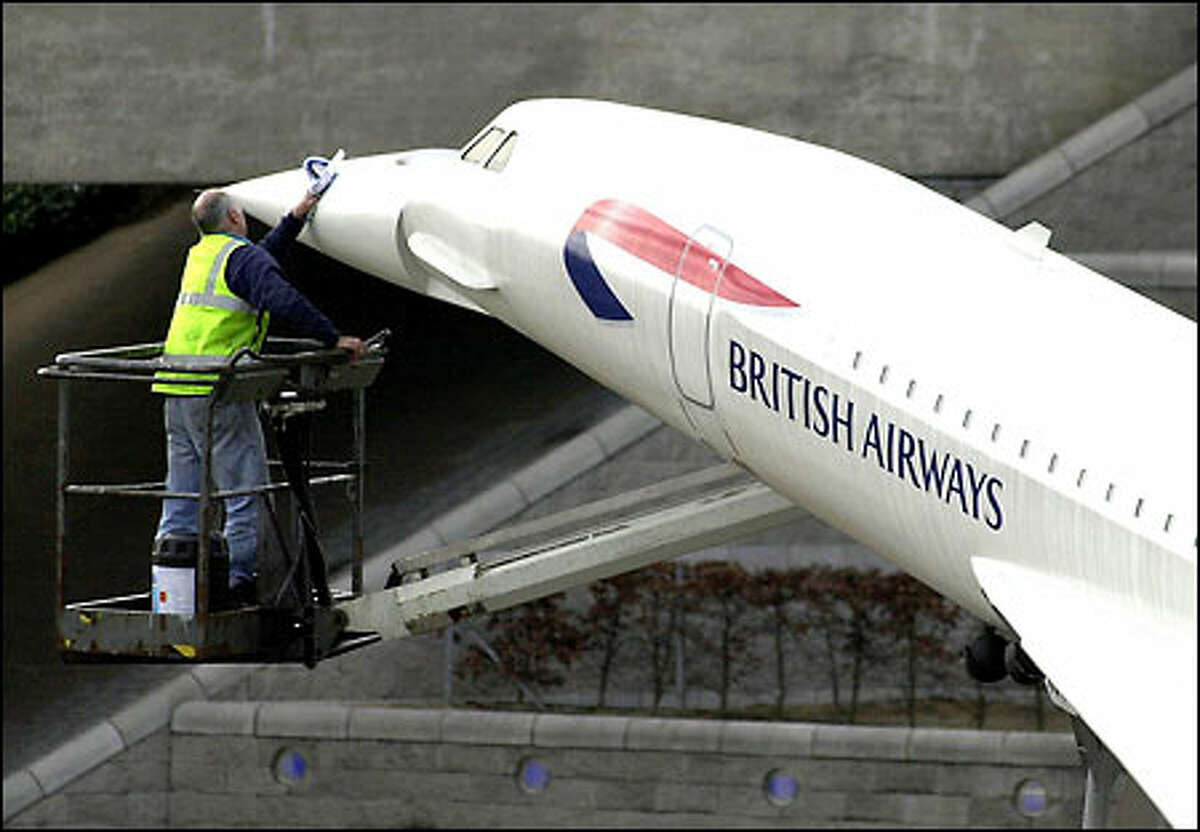 A British Airways worker cleans a model of the Concorde at the main entrance to London's Heathrow Airport yesterday. After years of pinning its fortunes to the deep pockets of business-class travelers, British Airways announced a strategic flip-flop, saying it would seek to compete with Europe's booming, low-cost airlines by offering cheaper travel over the Internet to passengers in coach. The airline also said it would cut 5,800 more jobs.