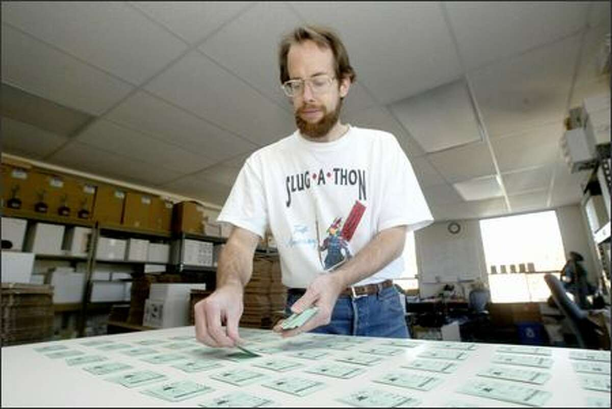 Toivo Rovainen collates game cards at the Cheapass Games office in Ballard. The company's games are sold nationwide.