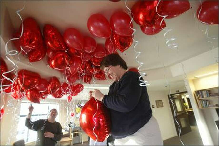 Rick Gillmore and Jeanne Lamont from the development office of Bailey-Boushay House on East Madison in Seattle prepare some of the 500 balloons for patients with AIDS and other life-threatening conditions. The annual Valentine's Day display is to thank volunteers, staff and the community for their support. Photo: Phil H. Webber, Seattle Post-Intelligencer / Seattle Post-Intelligencer