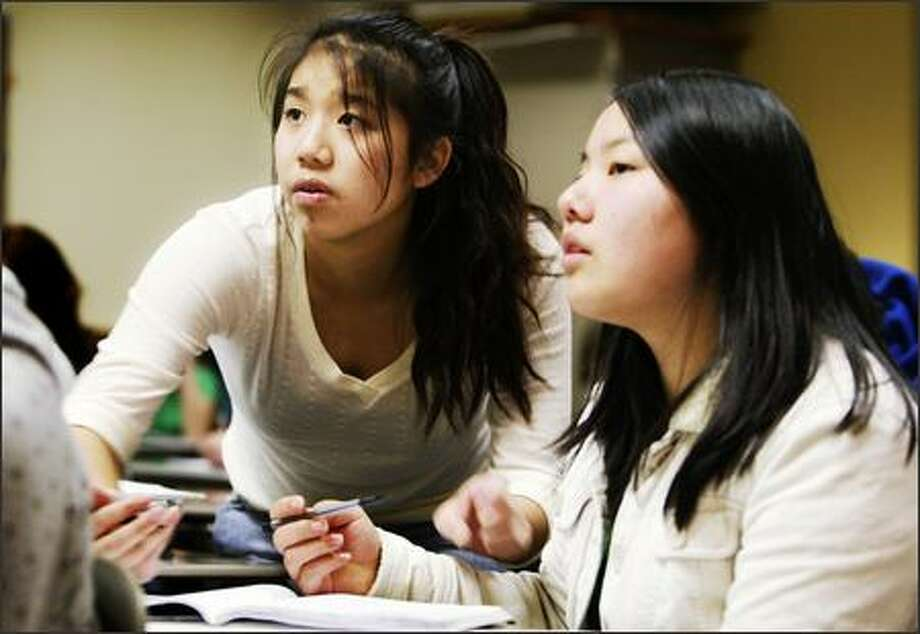 Ballard High School students Samantha Wong, left, and Annie Chu discuss an assignment in an advanced-placement language arts class Monday. State high schools have doubled the number of students taking such classes. Photo: Gilbert W. Arias, Seattle Post-Intelligencer / Seattle Post-Intelligencer