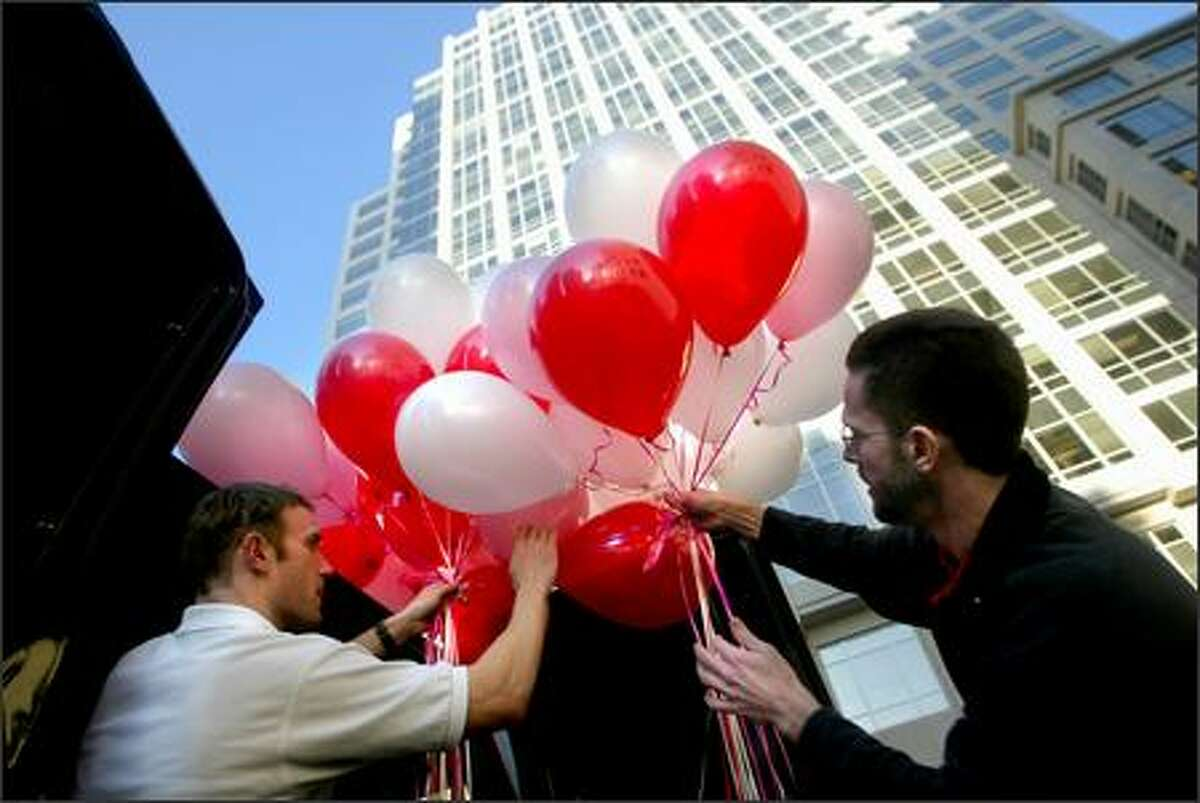 """Gerry Tonsor, left, and Craig Mathews from The Red Balloon Co. load a van full of balloons in Seattle on Monday. The company, which specializes primarily in balloon delivery and decorating, also sells gifts, cards, and retro toys. Manager Cameron Vail said business before this Valentine's Day has been """"extremely busy."""""""