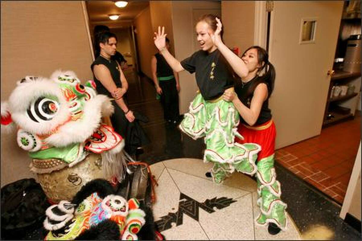 Lion dancers Shaney Mah, 11, left, and Linda Carey, 16, practice a maneuver before their performance at the Washington Athletic Club. Shaney, as the head of the lion, was the crowd's favorite.