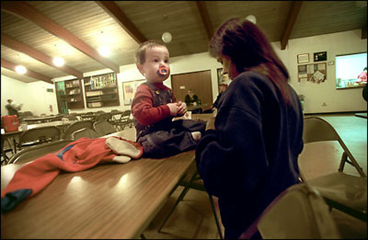 Stephanie Farrell dresses her 15-month-old son Sean-Patrick yesterday at an emergency shelter set up for dynamite-scare evacuees by the Red Cross.