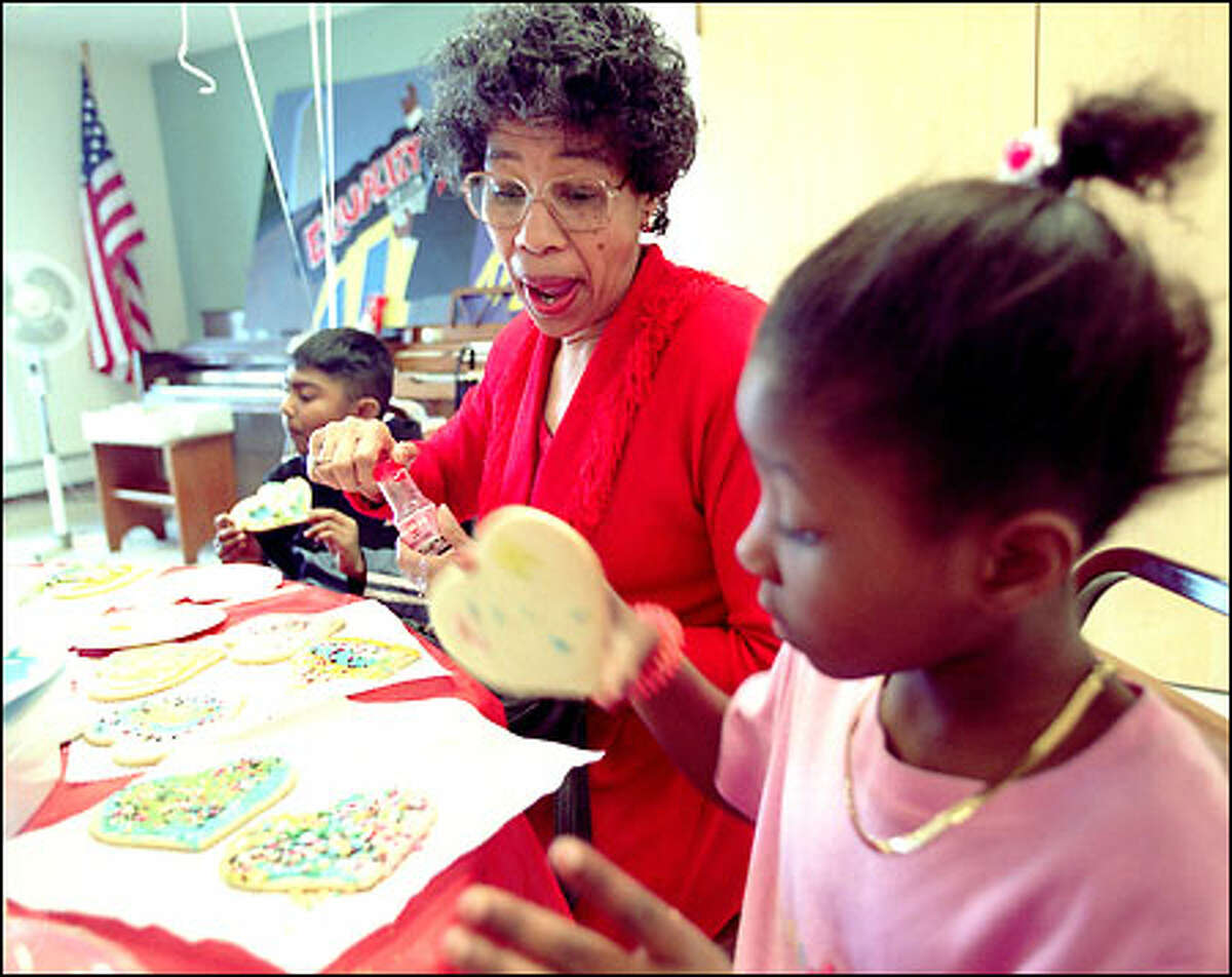 Joyce Muskelly, 66, reacts to Na'Tashianna Williams, 7, as she's about to turn her Valentine Day cookie into a cookie sandwich. In the background is Akash Lai, 7, eating his creation. Bailey Gatzert Elementary first graders visited the Central Area Senior Services Center yesterday for the Valentine's Day party and cookie bash.