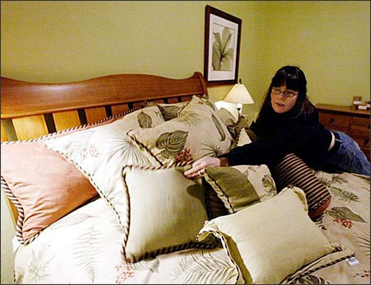 Designer Piper Lauri Salogga arranges pillows in a room of the feng shui house at the Home Show.
