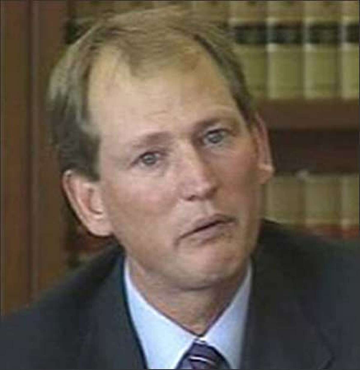 Former UW Coach Rick Neuheisel cries on the witness stand; photo taken from video.