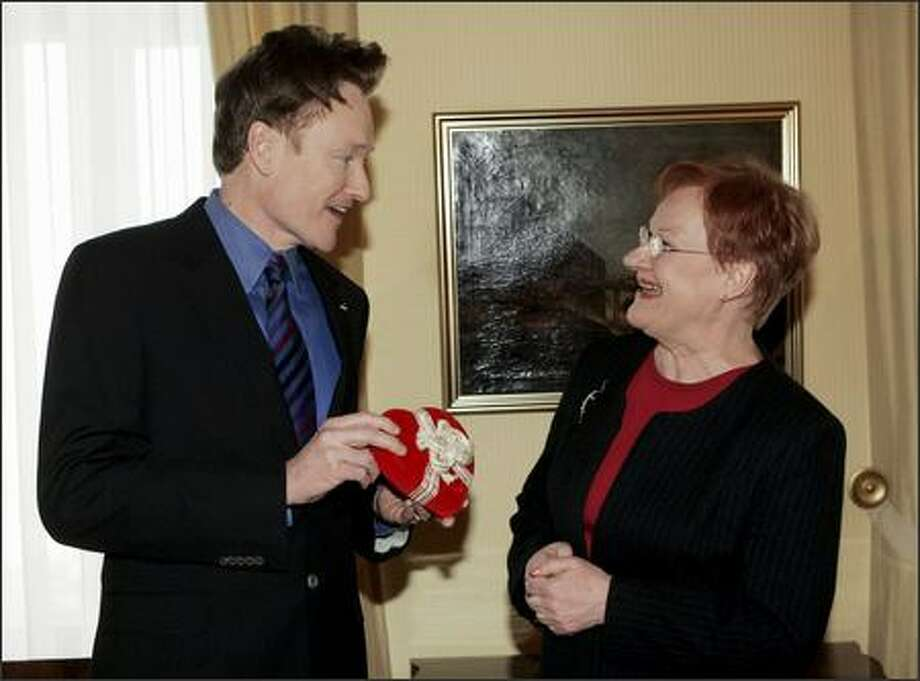 "Separated at birth, but together at last? ""Late Night's"" Conan O'Brien presents chocolates Tuesday in Helsinki to Finnish Prexy Tarja Halonen, who benefited from his distant support in her recent re-election bid. The talk show host boosted her candidacy with a mock ad campaign based on their similar look and red hair. Photo: Associated Press / Associated Press"