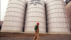Dave Kommes walks past grain elevators on Main Street in Washtucna, a town in Eastern Washington with 266 residents, no police, no money and bleak prospects.