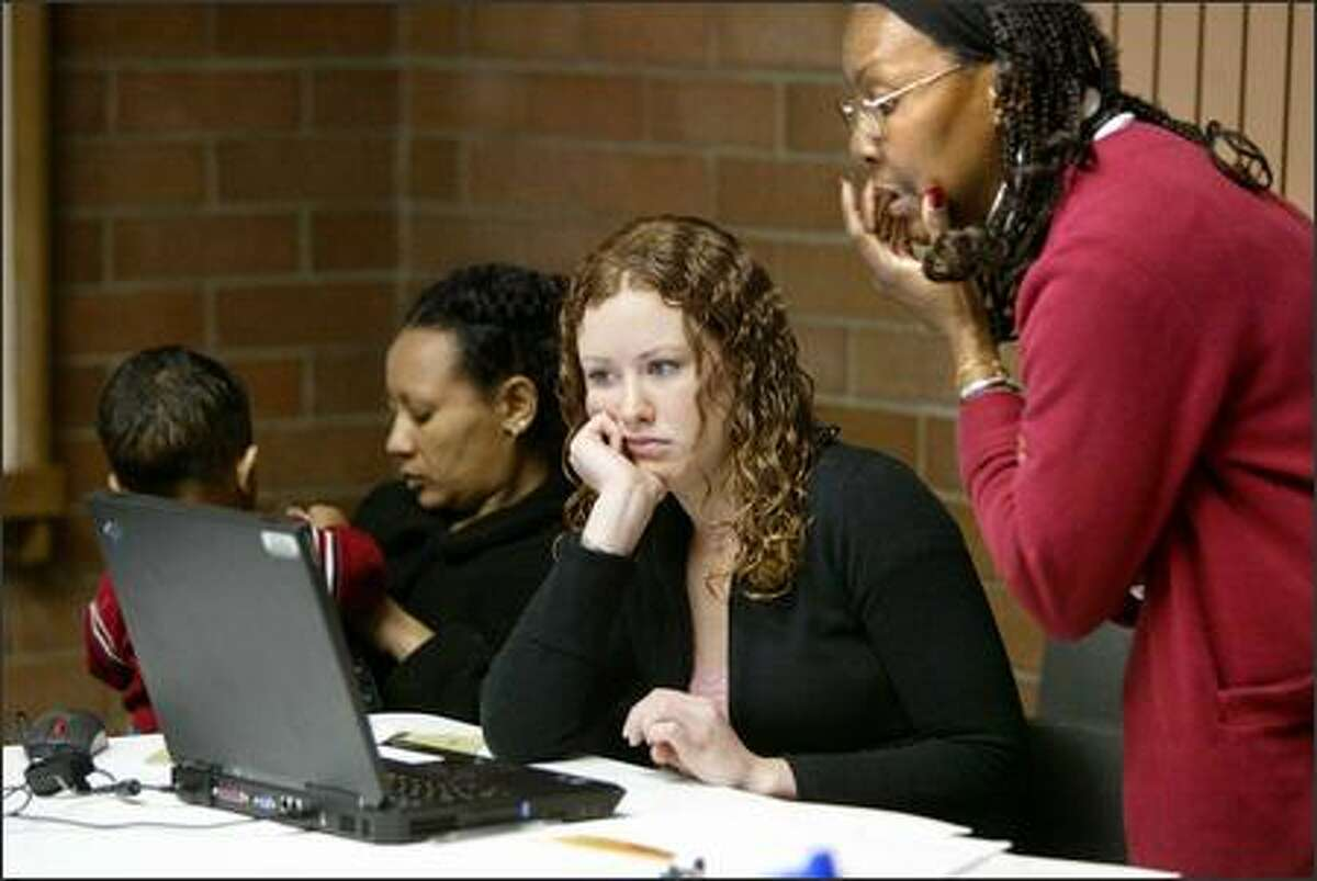 Tamera Kelly, center, and Andrea Shirley, right, work on preparing taxes for a woman at the library.