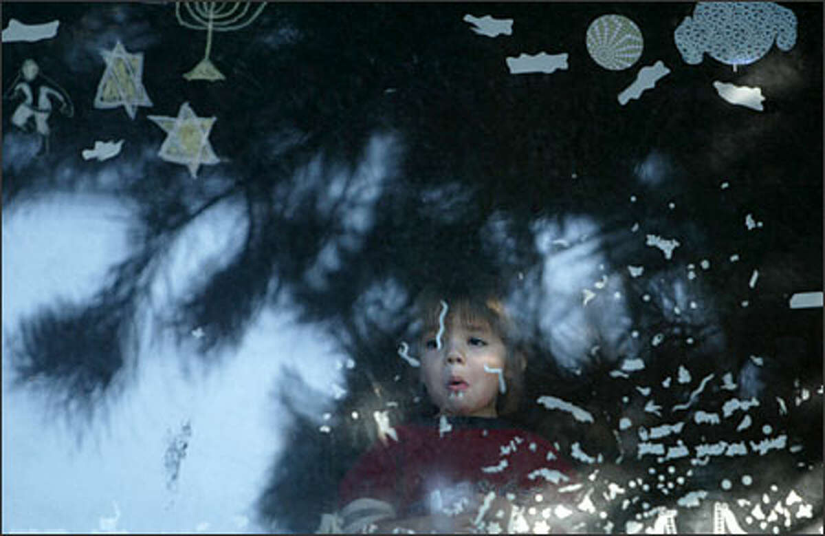 Under the Star of David, a child peers out a second floor window of their home at 1408 NE 65th St. as the FBI's Joint Terrorism Task Force conducts a raid. Agents arrested a neo-nazi tennant who lived in the apartment below from which a small arsonal of weapons was recovered on Tuesday.