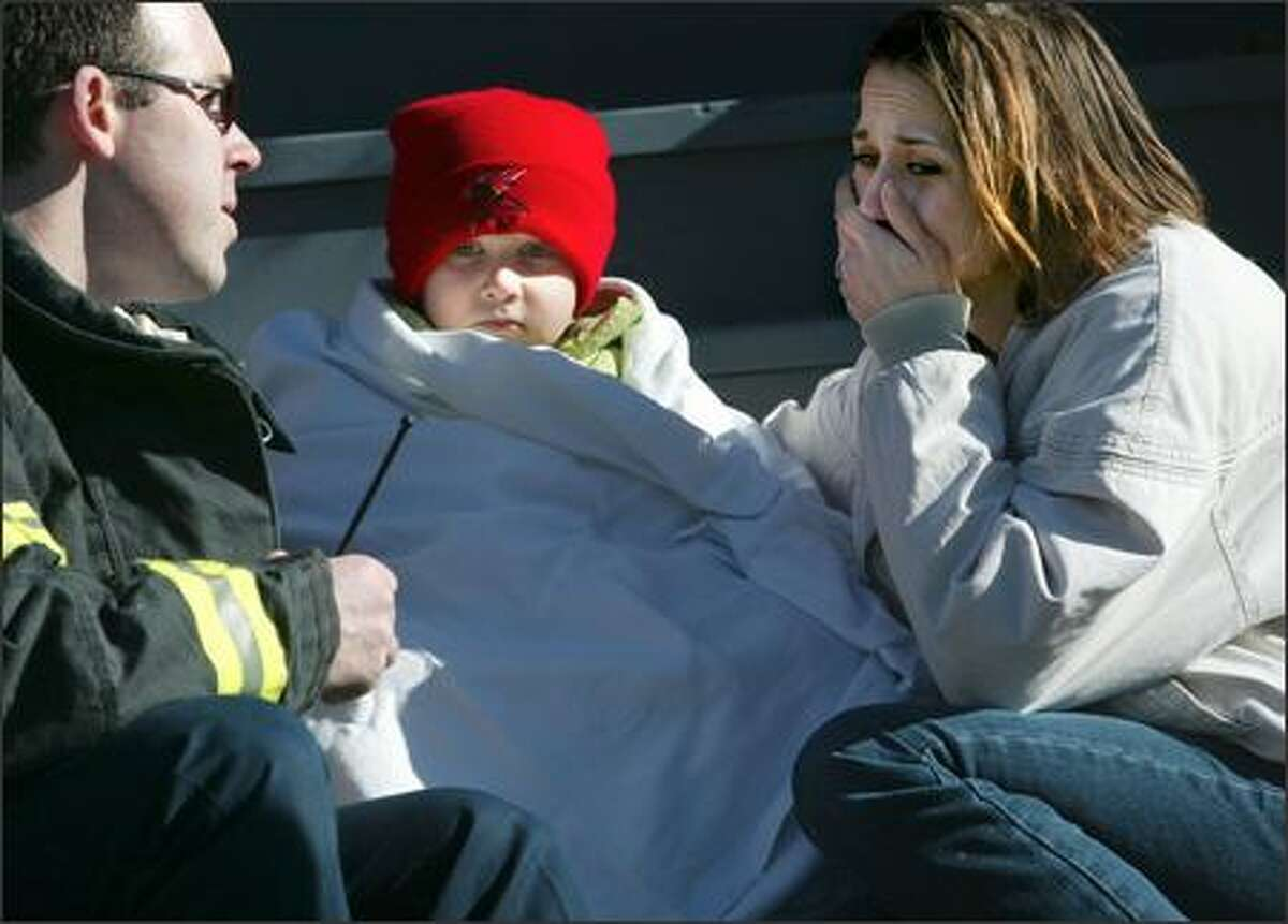 Mandie Sargent talks to Paramedic Zach Drathman as son Kameron sits with her on the steps of a neighbor's house as their own home burns on Boylston Avenue in the Eastlake neighborhood.