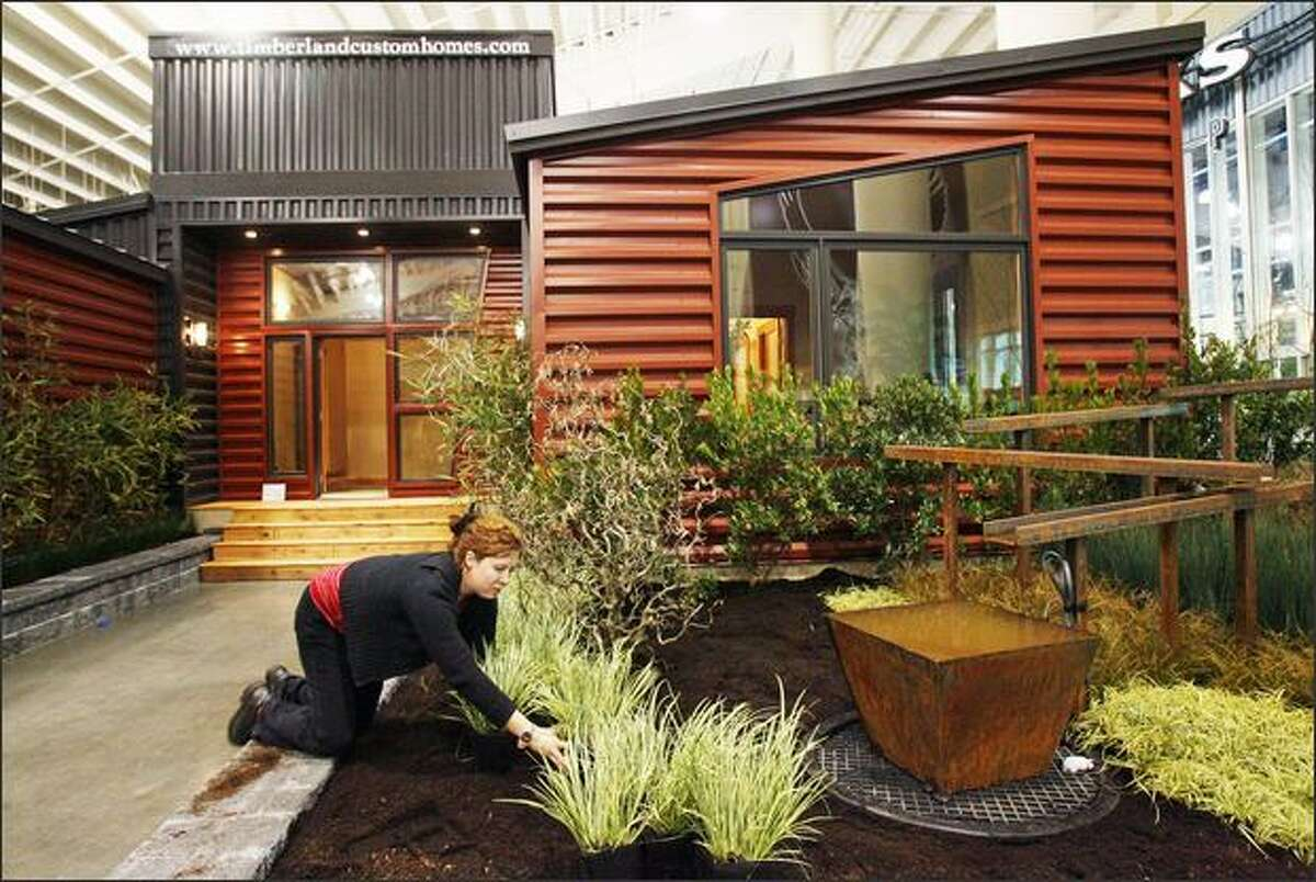 Debbie Ramos, a landscape designer for Malone's Landscape & Nursery in Kent, works on a garden outside a Timberland Home in preparation for the Seattle Home Show.
