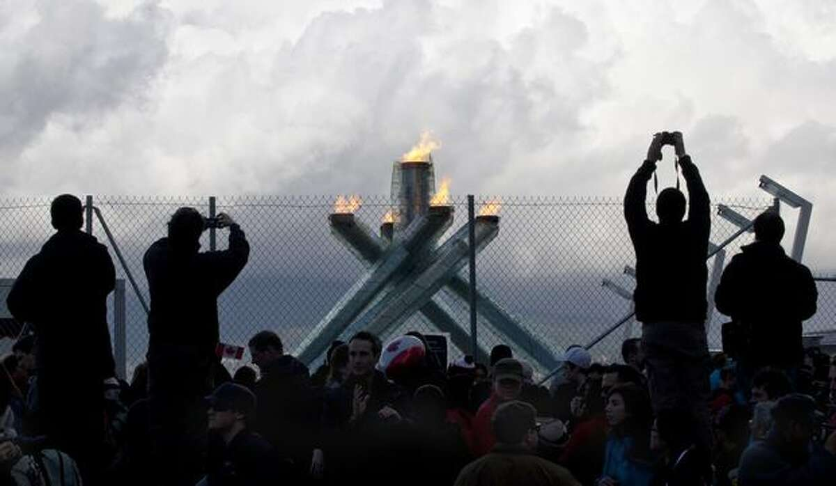 Spectators stand on cement barriers to take souvenir photos of the Olympic cauldron Sunday at the 2010 Vancouver Olympic Winter Games in Vancouver, B.C. (AP Photo/The Canadian Press/Paul Chiasson)
