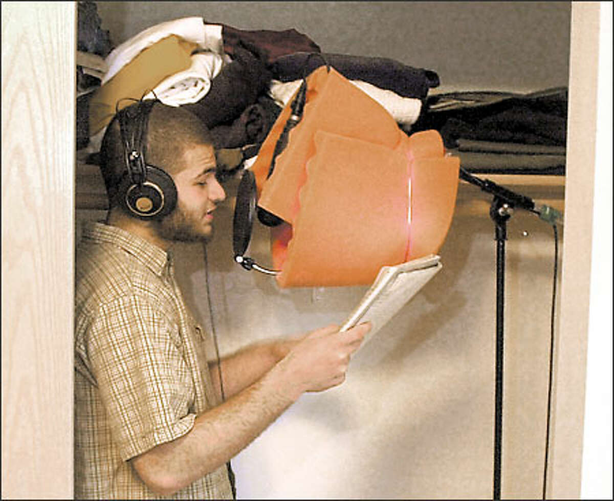 Abdul, 18, sings into a microphone in his bedroom closet during a recording session.
