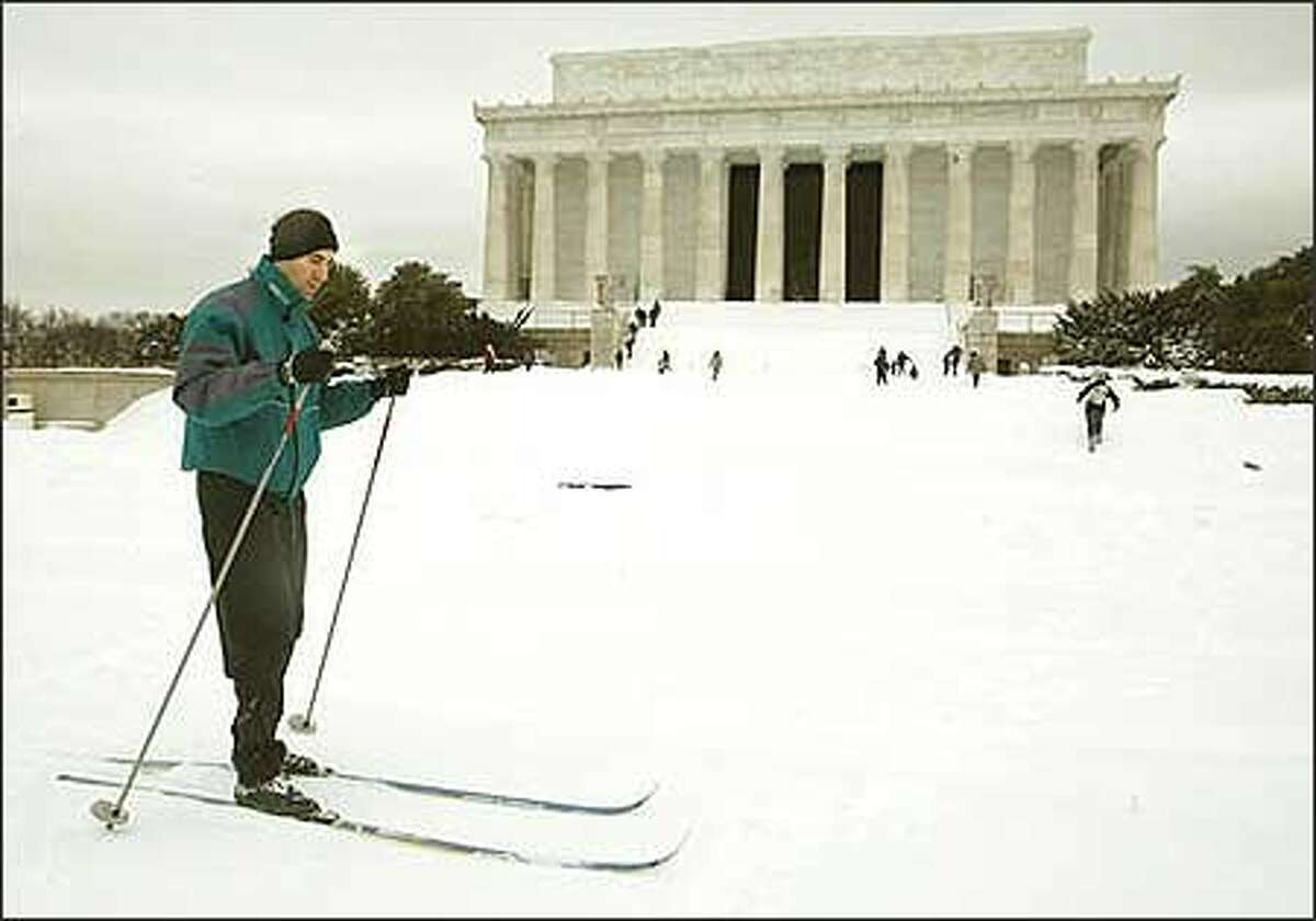 A man crosscountry skis past the Lincoln Memorial in Washington Monday, Feb. 17, 2003. Washington's worst winter storm in seven years dumped almost a foot and a half of snow on the nation's capital, crippling transportation and clogging the streets with snow for at least the next few days. (AP Photo/Charles Dharapak)