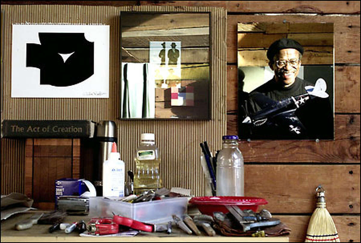 Abstract artist Weldon Butler is reflected in a mirror at his Madrona studio. At left hangs the original collage of his print