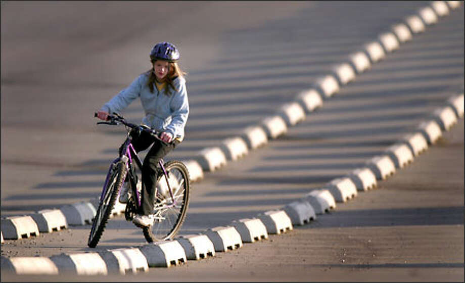 Mariah Schab, 12, of Monroe, weaves her bike between concrete wheel stops in a parking lot at Camp Casey on Whidbey Island during a family outing on Monday. Photo: Joshua Trujillo, Seattlepi.com / seattlepi.com