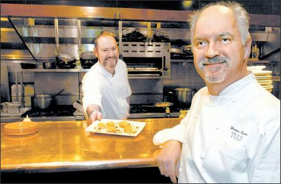 Thomas Dunklin, sous chef at Tulio Ristorante in the Hotel Vintage Park, delivers a dish to longtime executive chef and founder Walter Pisano, right. Photo: Grant M. Haller, Seattle Post-Intelligencer / Seattle Post-Intelligencer