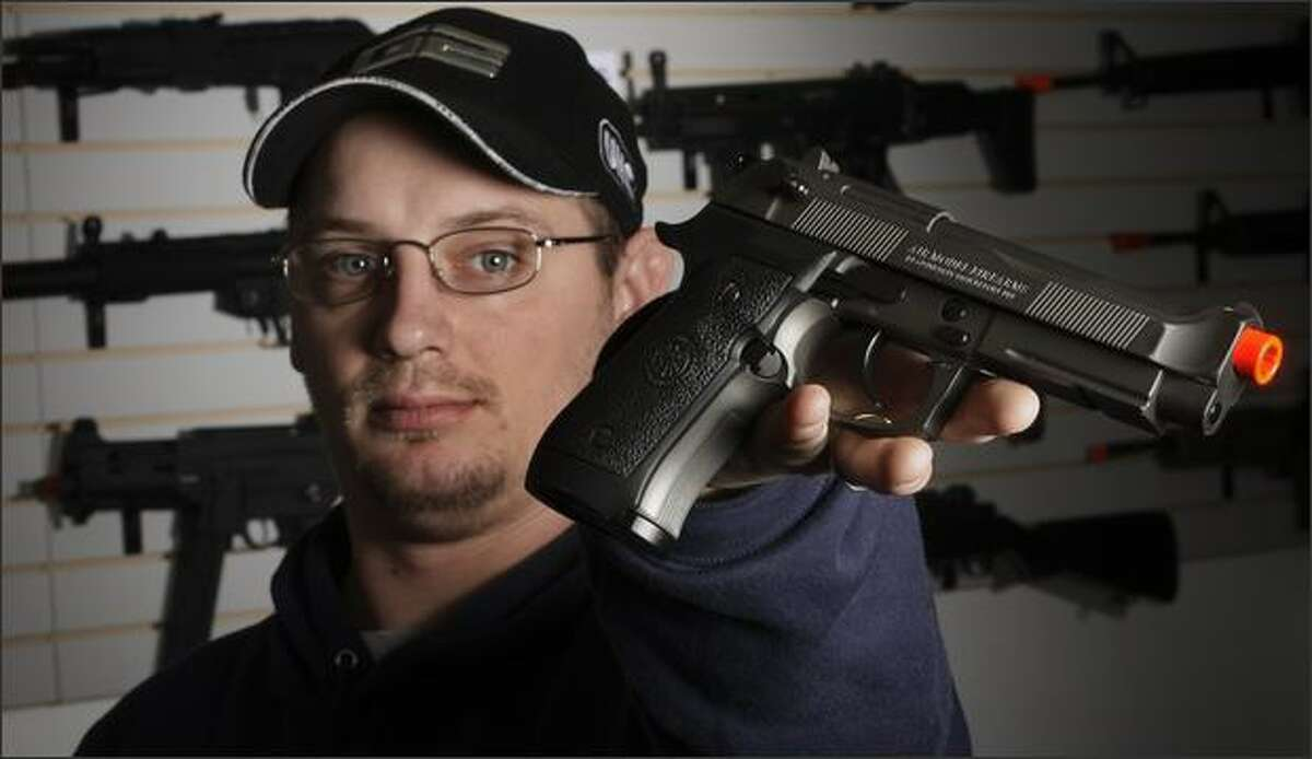Jason Pfingsten, owner of Pacific Rim Airsoft in South Seattle,shows a Airsoft semi-automatic pistol designed to look like a real Beretta.
