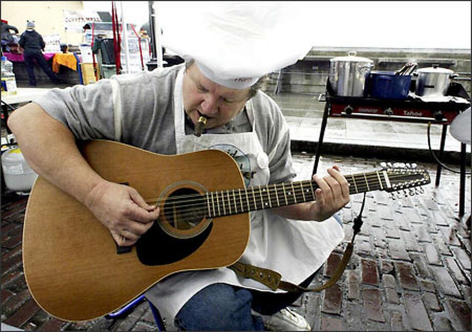 Harry Smith from Haute House BBQ strums his guitar while waiting for his chili to cook. Chili folks were outnumbered by the pitmasters at the Market. Photo: Jim Bryant, Seattle Post-Intelligencer / Seattle Post-Intelligencer