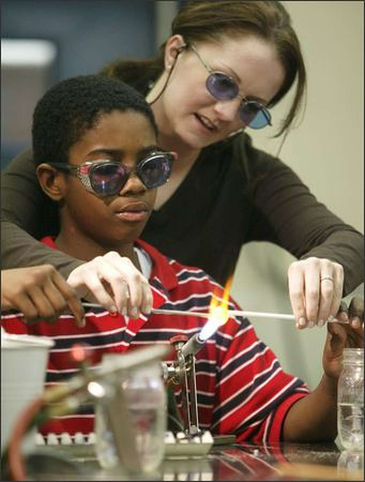 Stacy Frost, an instructor at Pratt Fine Arts Center, helps Washington Middle School student Carl, 12, get started on his glass creation. Frost says the quality of work by the boys