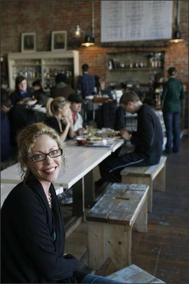 Chef Ericka Burke sits in the transformed Oddfellows club, where the historic space retains its weathered appeal. The light-filled room draws all ages. The menu is populated by comfort food. Photo: Meryl Schenker, Seattle Post-Intelligencer / Seattle Post-Intelligencer