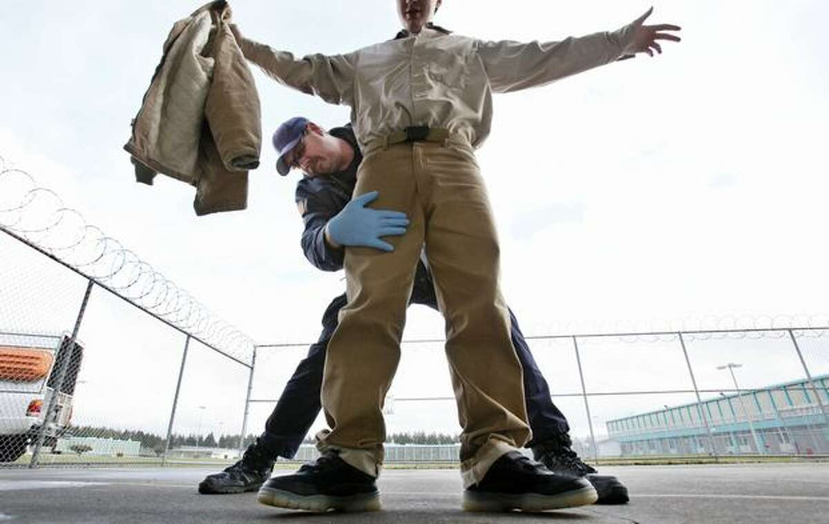 Correctional officer Ken Kleinworth frisks an inmate leaving a dining hall at the Washington Corrections Center in Shleton last Thursday. The population of Washington state prison inmates has become whiter, older and more violent in the past decade, an Associated Press review of Department of Corrections records has found. And while running the prison system eats up 5 percent of the state budget, there appear to be few places that can be cut without having to resort to releasing inmates early, as some states have done to balance the budget. (AP Photo/Elaine Thompson)